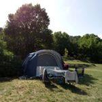 Tenda all'ombra di un albero dalle foglie viola nella piazzola del Camping La Genziana