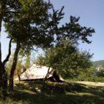 Una tenda in mezzo agli alberi del Camping La Genziana