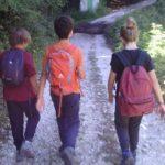 Tre bambini visti di spalle, zaino in spalla e passo spedito verso la vetta della montagna